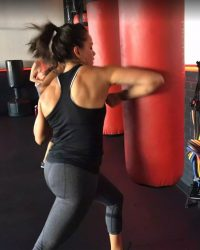 Fit In 42 Fitness Gym - Female member hitting punching bag