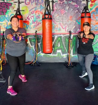 Fit In 42 Fitness Gym - Lean mommy makeover - Female members smiling working out with stretch bands