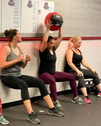 Fit In 42 Kingwood Texas Gym members doing wall sit with ball exercise