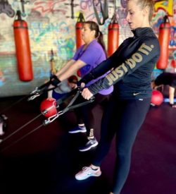 Personal Trainer and woman pulling bands - Fit In 42 Studio Gym